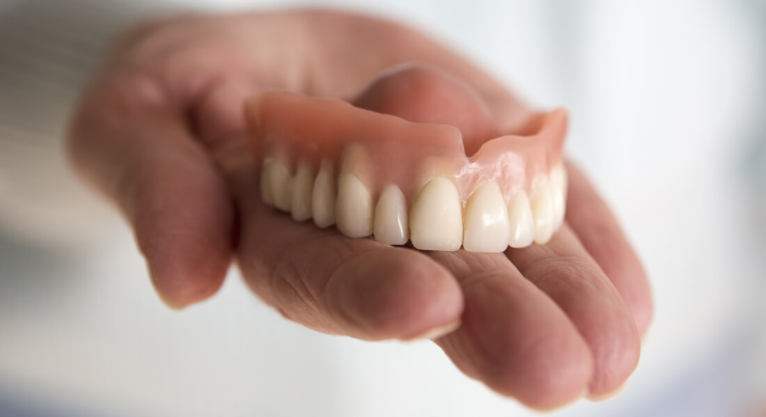 dentures in dentist's hand
